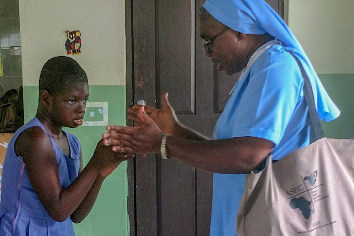Sr. Francisca Damoah, SIJ, ASEC Regional Director West Africa, plays with a child at St. Elizabeth Day Center for Children & Young Adults with Disabilities, Ghana, during a site visit (June, 2018).