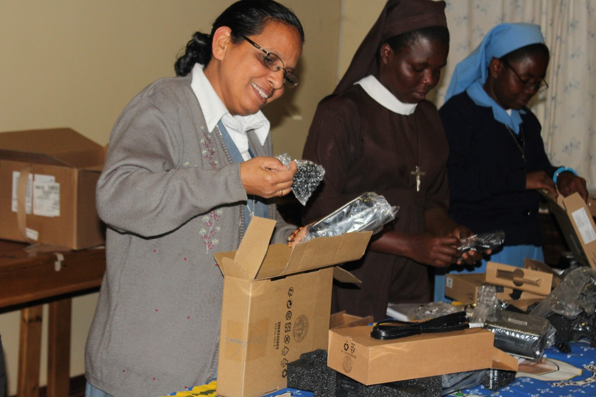 Sr. Elsamma is all smiles as she unpacks her new laptop provided by ASEC's generous funder, Conrad N. Hilton Foundation.