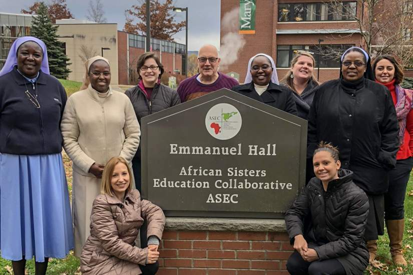 Sr. Draru (left) and ASEC U.S. staff pose for a photo with Sr. Joan Chisala, CSJB (standing, second from right) during her visit to ASEC headquarters in Scranton, PA (Nov. 9, 2018).