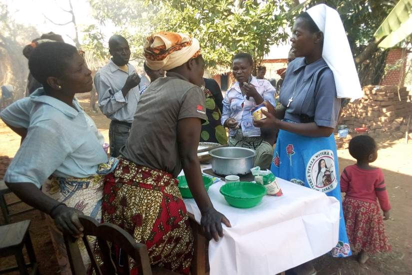 Sisters offer training support groups to the Bembeke community of individuals diagnosed HIV positive. Here a sister demonstrates food preparation using local resources for healthy living.