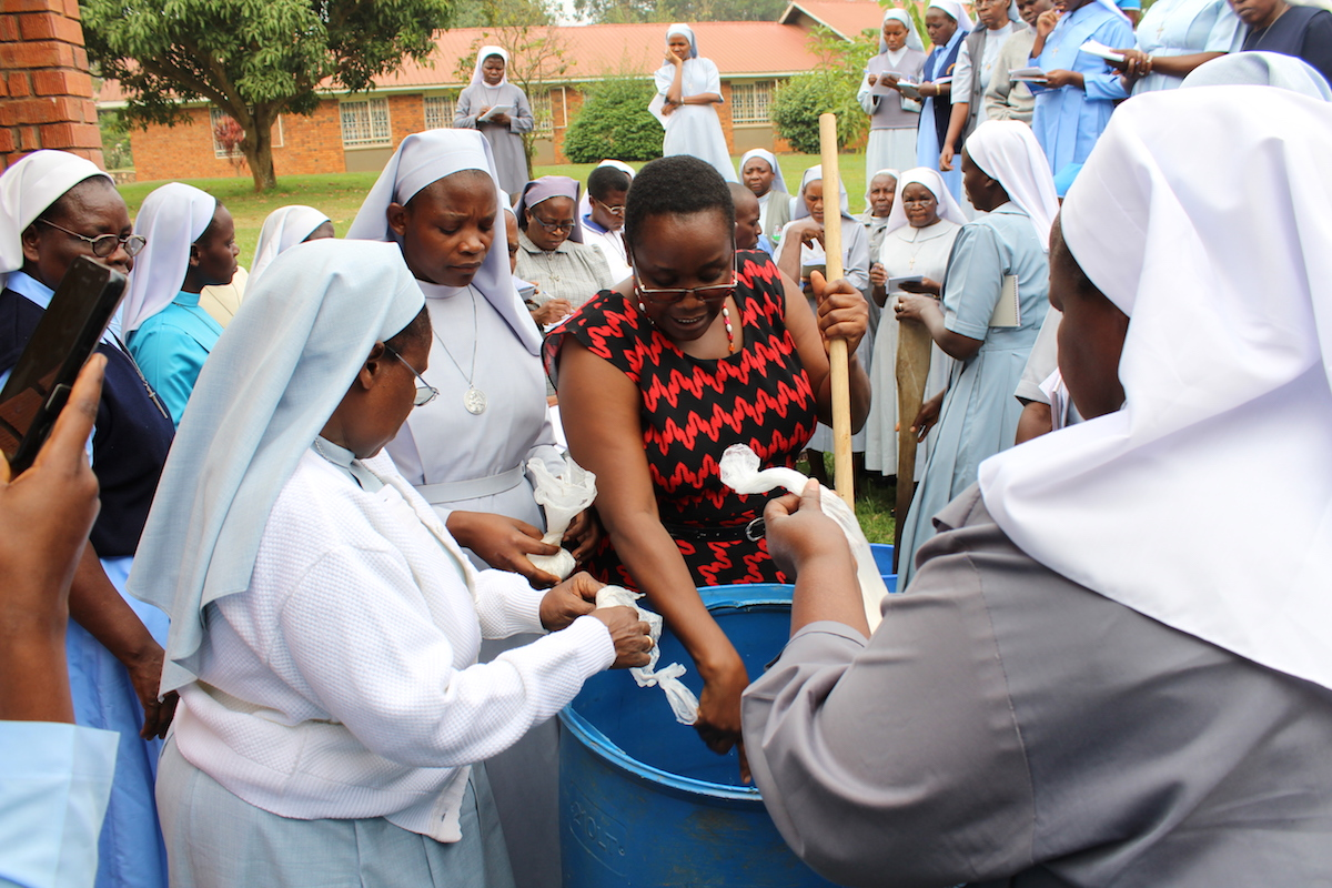 Caroline Bonareri Tirisa shows the sisters how to make liquid soap.