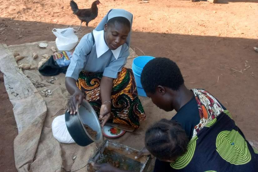 A Teresian Sister demonstrates how to prepare fresh juice.