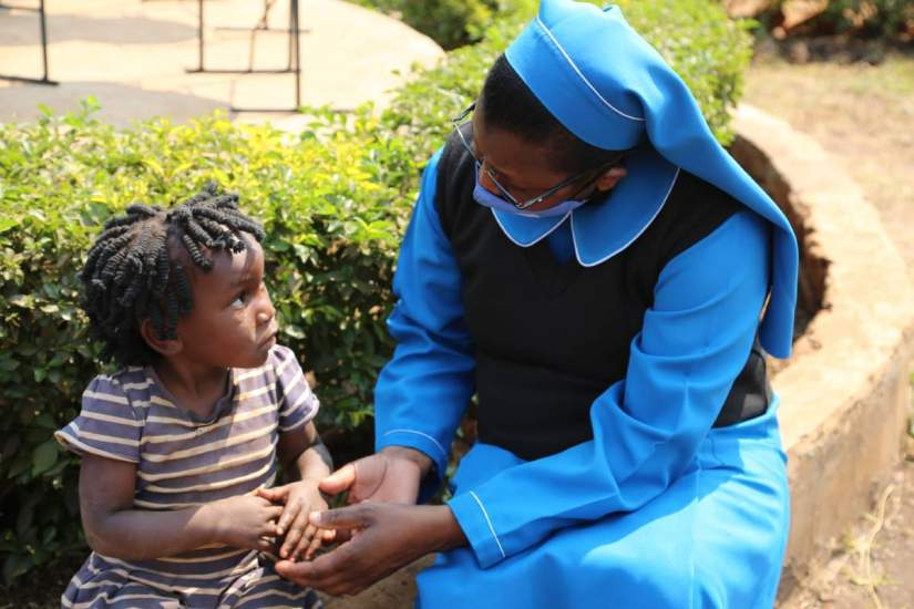 ASEC Program Director Sr. Juliana Zulu, RGS, shows the love and care of a sister to a little girl in Zambia.