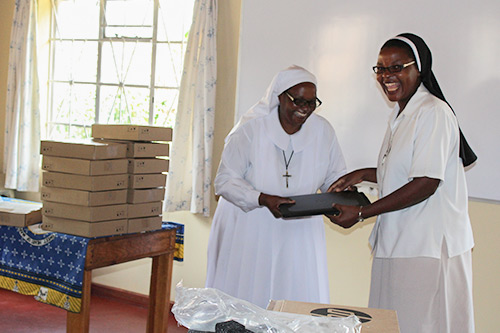An overjoyed sister in the SLDI administration track, Malawi, receives her new laptop during the opening ceremony of the workshop.