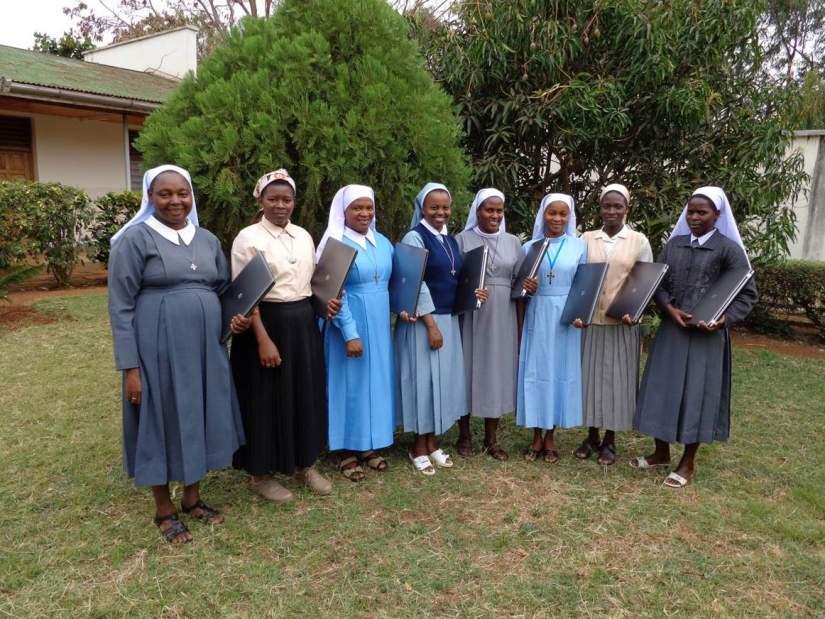 Sisters stand together at their HESA orientation presenting their new laptops (from L-R) Sr. Pelagia Chimpa, Sr. Magreth Kiria, Sr. Restituta Msemwa, Sr. Spesioza Massawe, Sr. Agripina Fidelis, Sr. Efrosina Mbiki, Sr. Venosa Mshana, Sr. Yustina Yilima