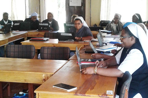 Malawian sisters in the SLDI program practicing computer skills in class.