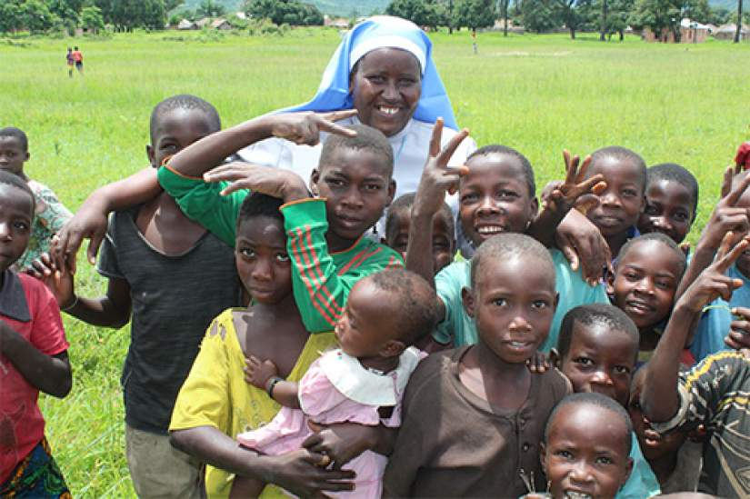 Sr. Maria Telesphora (COLU), ASEC Coordinator – Tanzania poses with children in Sumbawanga.