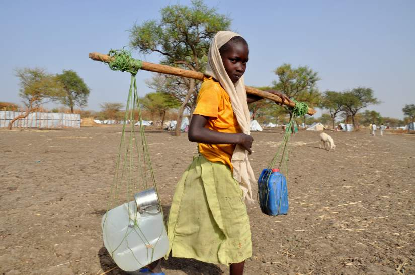 Women and girls spend several hours a day collecting water, often standing in baking heat. They then carry the heavy jerry cans home, either on their heads or tied to the end of poles.