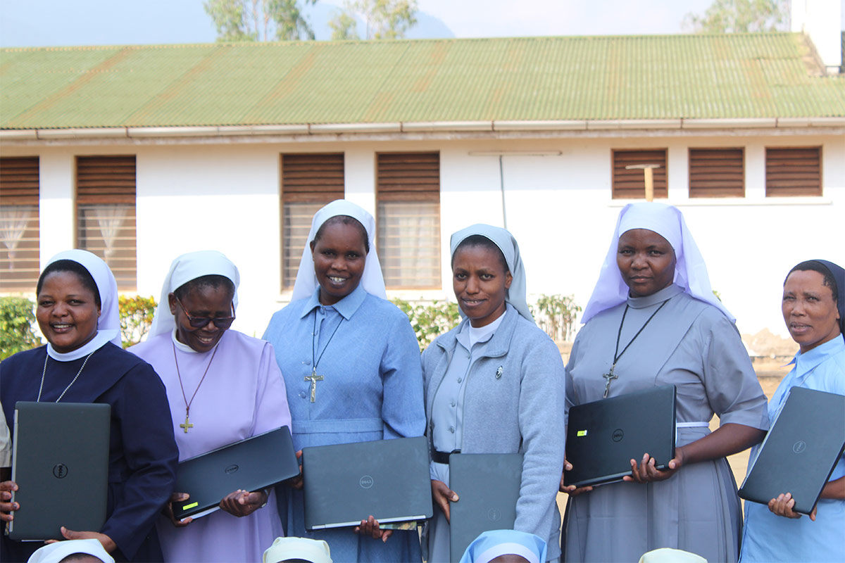 Sr. Constansia (2nd from left) looks at her laptop with a smile during the SLDI Finance Track II Workshop that took place in Tanzania from August 12 - September 9, 2017.