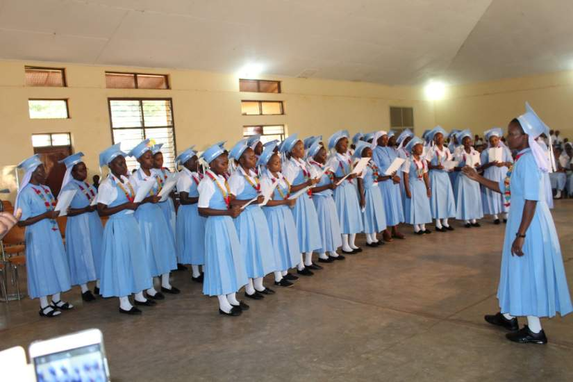 The form six graduate students with their headmistress at the centre Sr. F. Mkwizu at Bigwa Secondary school Tanzania singing during graduation ceremony on April 26, 2017