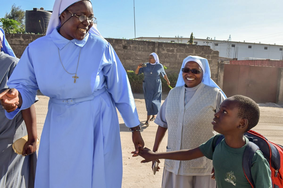 ASEC Executive Director Sr. Draru greets a 9-year-old girl returning from school in Dar es Salaam, Tanzania. They talked about her day at school while they watched the other Sisters sing and dance in the street.