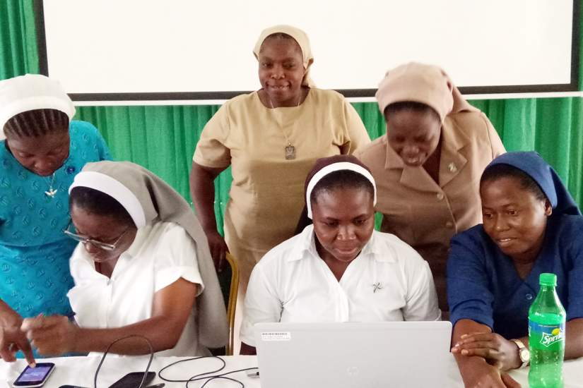 Sisters studying at the Sacred Heart School of Nursing work together with technology as Sr. Clementina Obembe, OSF, ASEC's Regional Director West Africa, looks on with pride.