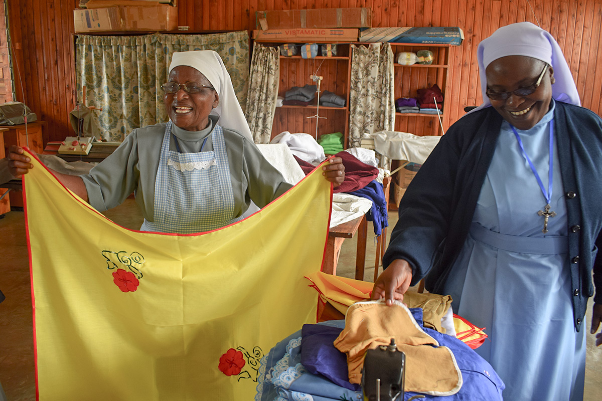 The CNDK sisters holding garments from their clothing and fabric manufacturing business in Huruma Rombo, Tanzania.