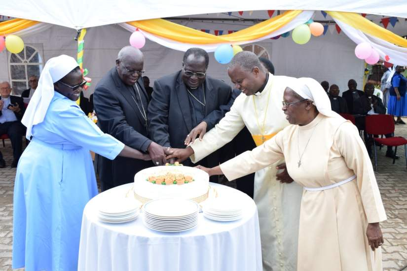 Archbishops John B Odama & Emmanuel Obbo and religious cut cake at ARU Golden Jubilee launch (November 8, 2017).