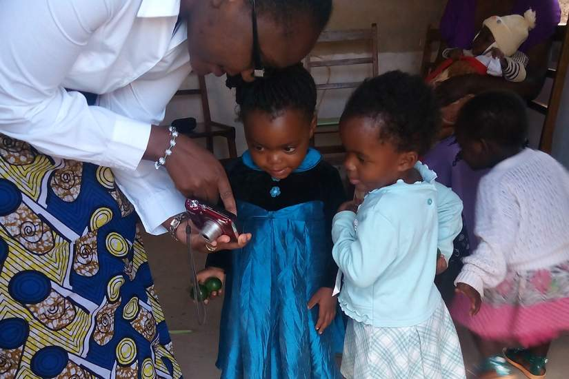 Sr. Astridah shows the children a photo on the camera.