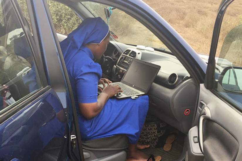 Sr. Clarisse Remjika Jaiwo, ASEC Director, Cameroon, searching for an internet connection on the side of the road.