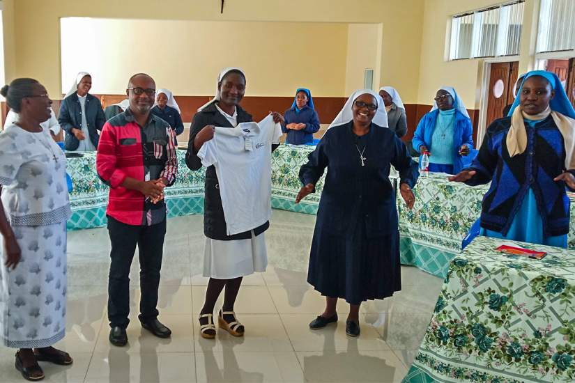 During the HESA Reflective Learning workshop in Malawi, Sr. Evarista (holding shirt) received recognition for maintaining the rank of top student at the Catholic University of Malawi for five consecutive semesters.