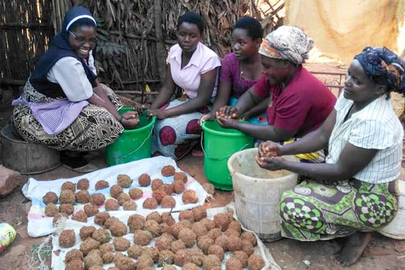 Sr. Jane teaches her sawdust briquette recipe to the women in her community. It has long been a dream of these Malawian women to find an alternative to firewood.