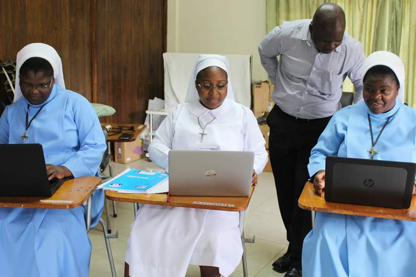 Sisters Christine, Sampa and Mwila participate in an exercise on computer and communication skills with the supervision of Mr. Adam Daka.