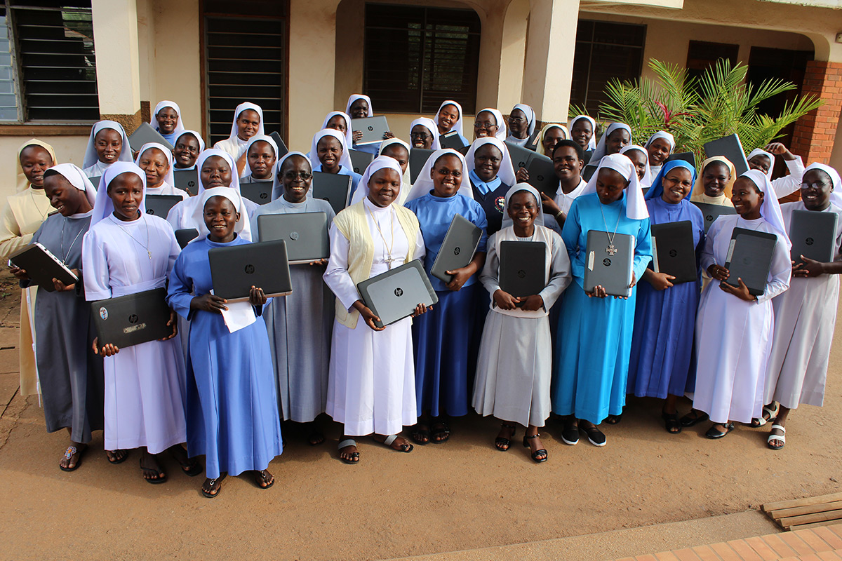 Sisters attending the online-onsite orientation at St. Augustine Institute Kampala, Uganda pose for a group photo holding their new laptops.