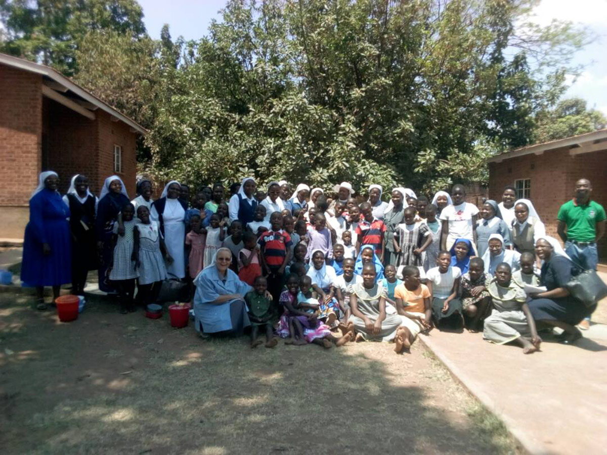 Sisters pose with children from the St. Mary's Rehabilitation Centre in Chezi, Dowa during the SLDI workshop field trip. At St. Mary's, sisters of Mary Mediatrix are taking care of malnourished children and orphans.