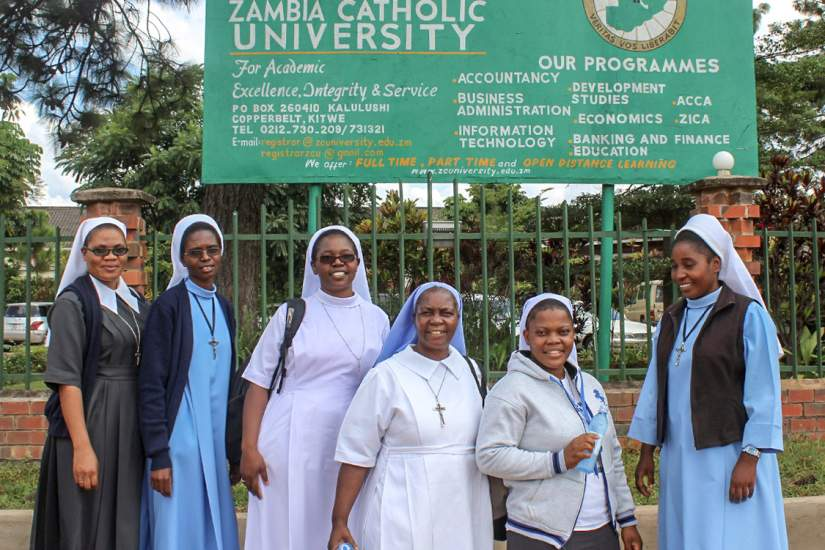 HESA students of Zambia Catholic University pose for a photo under their alma mater's sign.