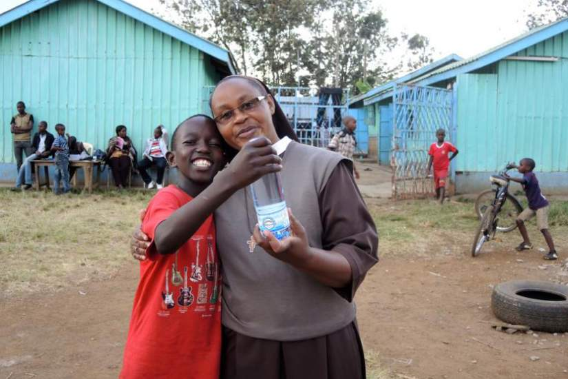 Sr. Catherine Wanza holds a bottle of the Ukweli Oasis Drinking Water with Kennedy Mwaura, 15, the class poet. The water bottling project is an income-generating project to help support school fees for more than 100 boys a year. (GSR photo / Melanie Lidman)