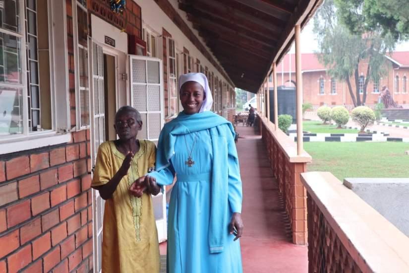 A Good Samaritan Sister walks with an elderly resident of Mapeera Home.