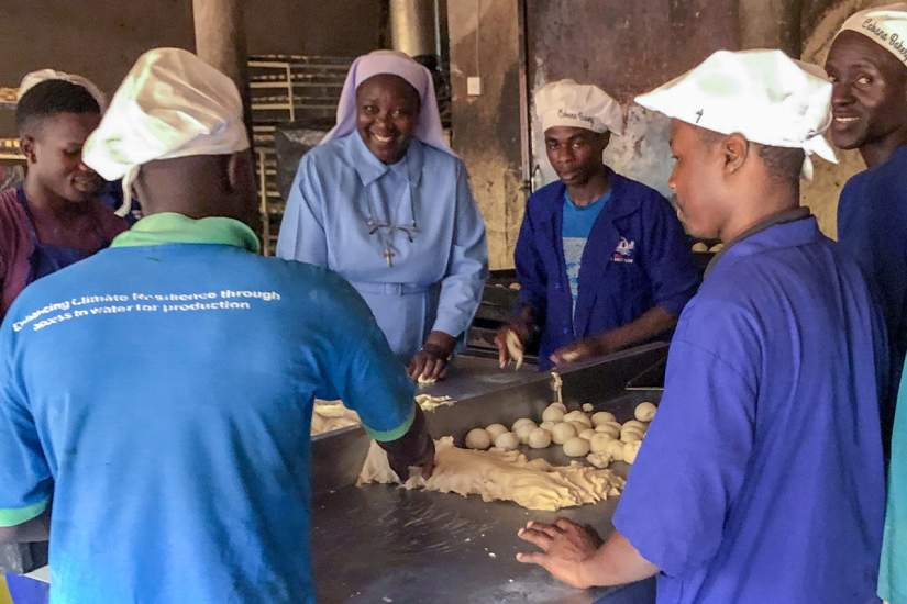 During a site visit in June, 2019, ASEC Executive Director Sr. Draru Mary Cecilia, LSMIG (center), learns the break-making process from bakery staff.