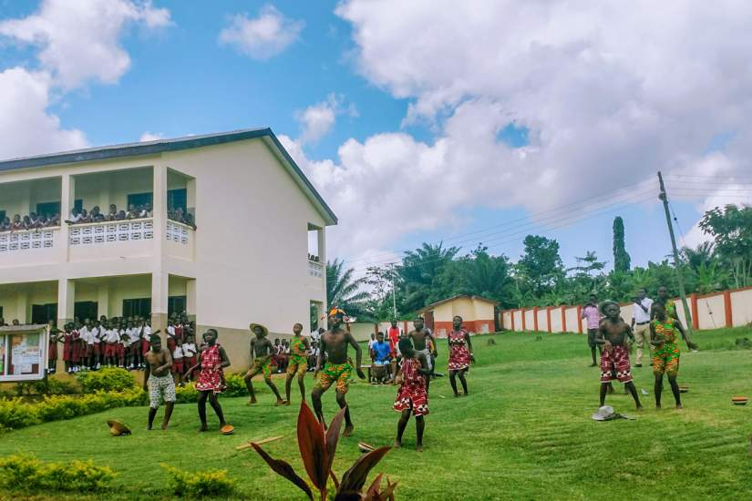 Students at Infant Jesus Preparatory school greet ASEC staff with song and dance (June 2018). Funding for the new wall (behind the students) was secured by SLDI alumna Sr. Irene Christine Oparku.