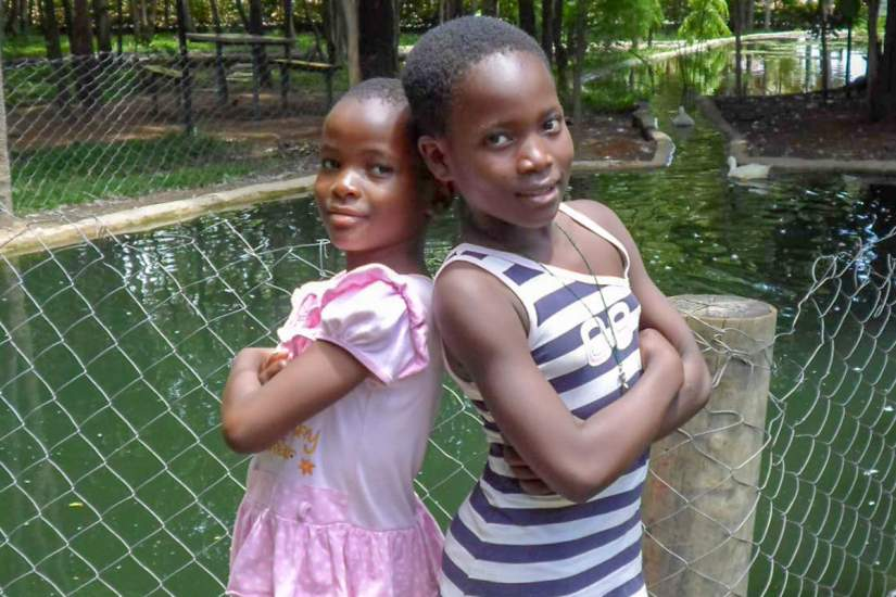 Younger sister Margaret (pink dress) and big sister Cecilia (stripes) pose for a photo. Because of the acts of Good Samaritans, Margaret and Cecilia are now thriving. Today the two sisters are very responsible, hardworking girls.