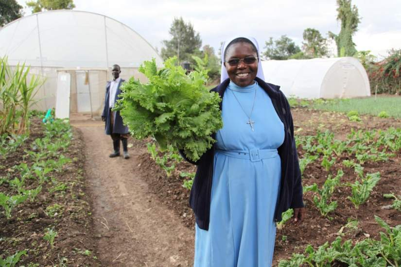 Sr. Catherine Owormungu shows off lettuce from the greenhouse farming project – increased food production to feed children in their schools.