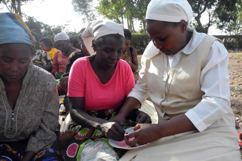 Sr. Josephine, right, helps a woman make a bangle bracelet. Image courtesy of Global Sisters Report (GSR).