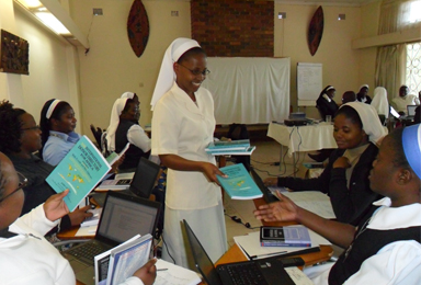Sr.-Maureen-Malashya-distributing-text-books-and-Laptops-to-the-SLDI-Finance-Track-I-at-Kalundu-Study-Centre