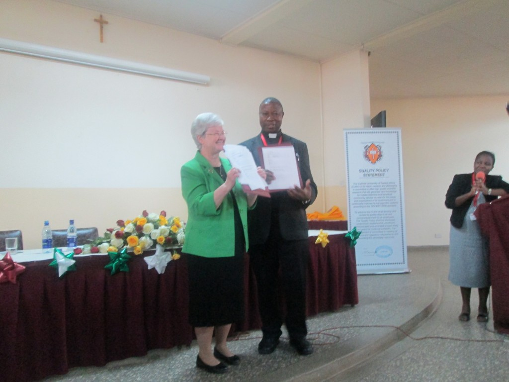Sr. Anne Munley, IHM, Ph.D. and Rev. Dr. Pius Rutechura stand together displaying the signed MOU
