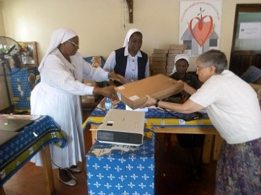 Sr. Selina Chimzukira receiving a Computer from Sr. Gail and Sr. H. Chombo