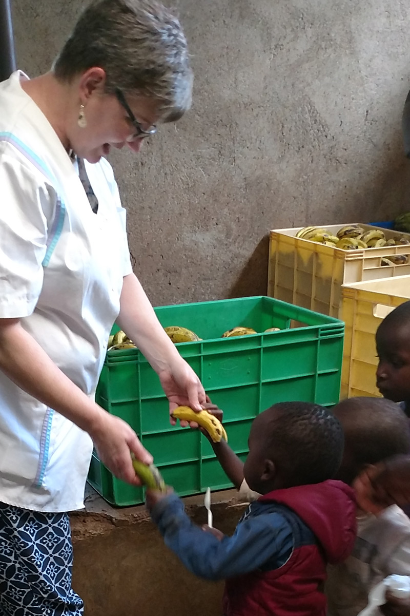 Service Learning trip chaperone Jacqueline Reich of Chestnut Hill College hands out bananas to a young boy in line at the St. Martin's feeding program in the Nairobi slums.