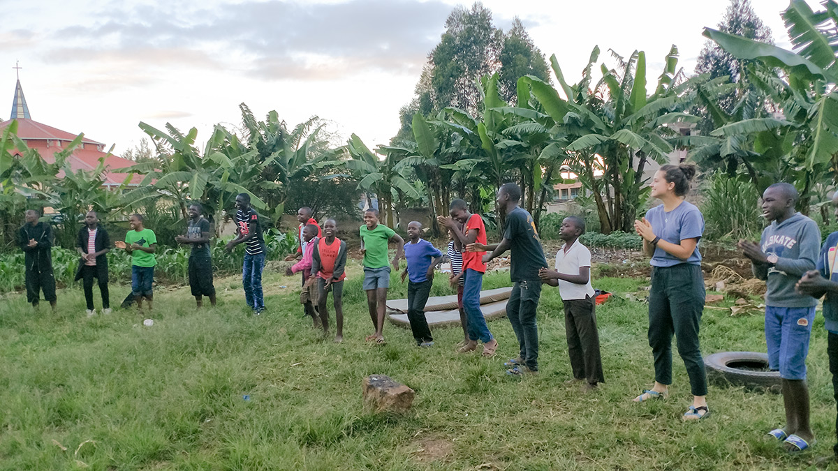 Students are playing a dancing game with street boys from the Ukweli Home of Hope.