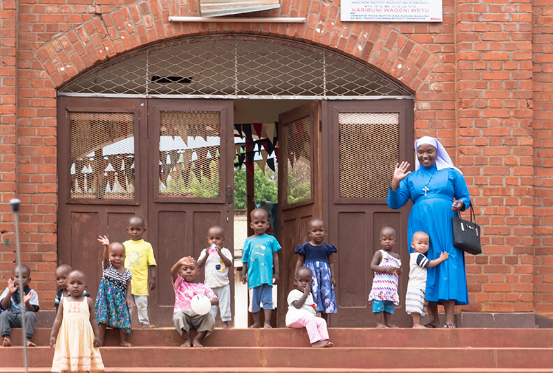 Mgolole Orphans waving on the stoop